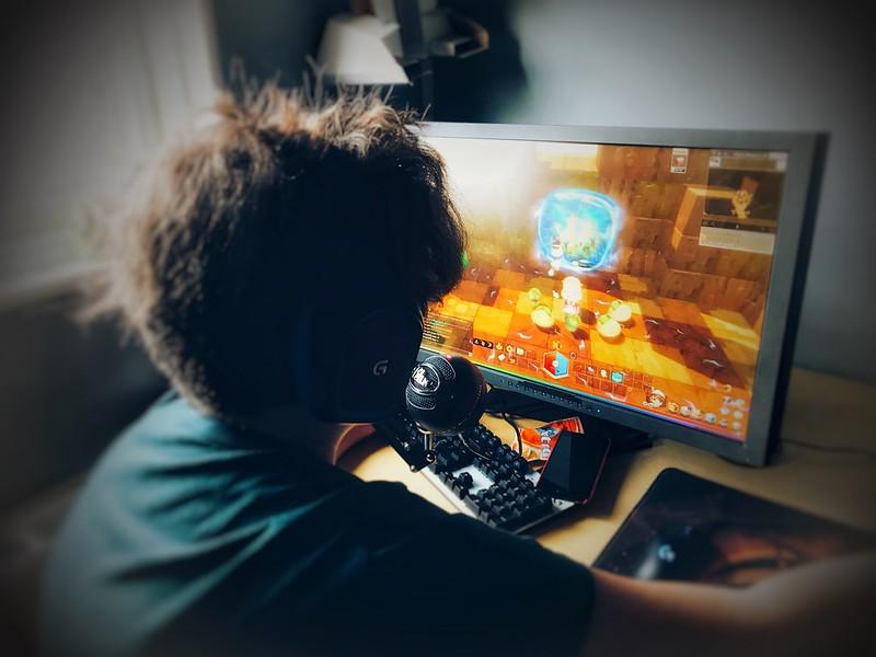 garoto de headphones jogando jogos eletrônicos em seu computador