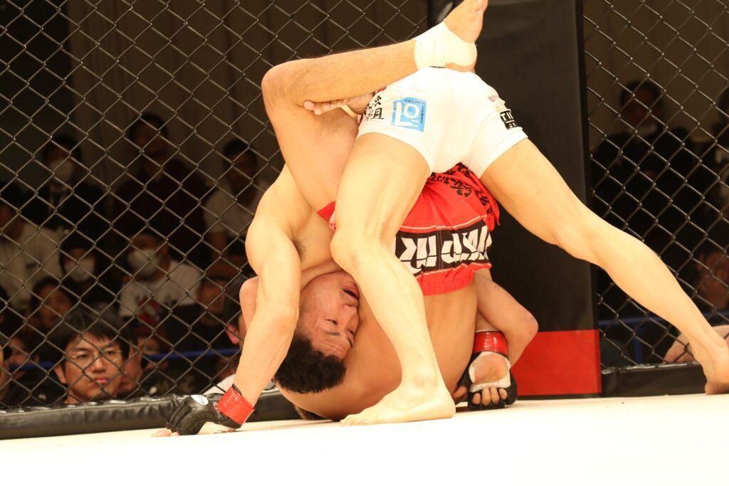 em luta de mma lutador encaixa uma guilhotina em seu oponente apoiado na grade