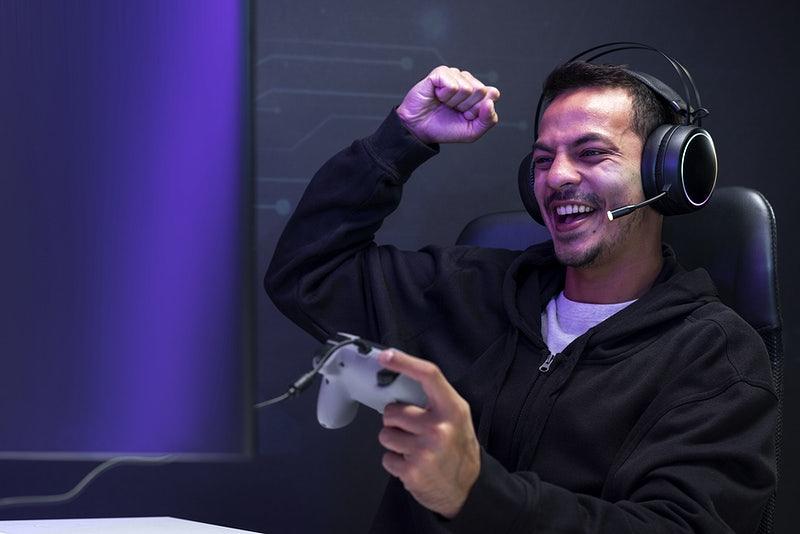 Um jogador segura um joystick e comemora sorrindo