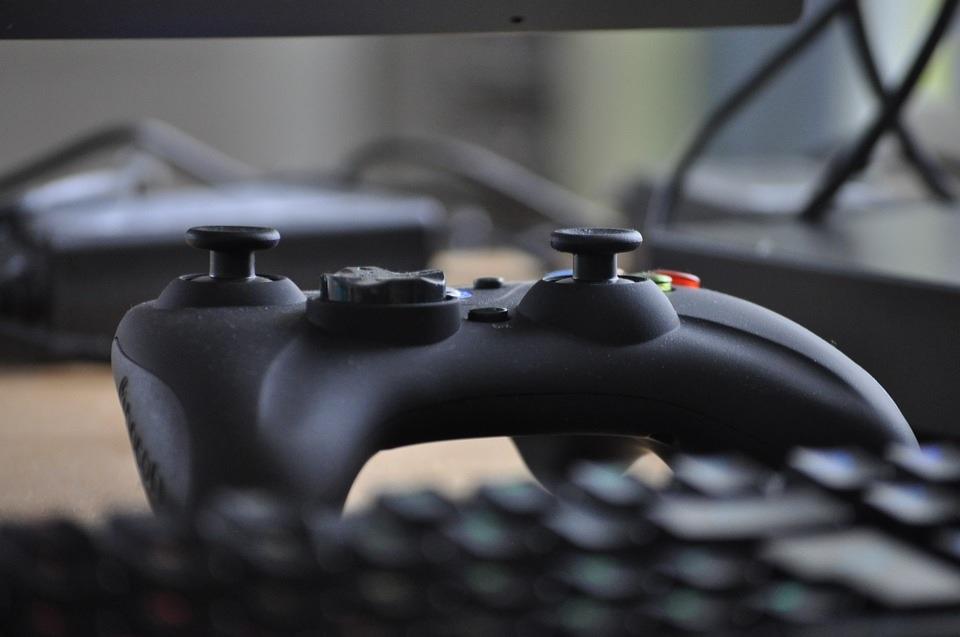 Um joystick está sobre uma mesa com teclados de computador