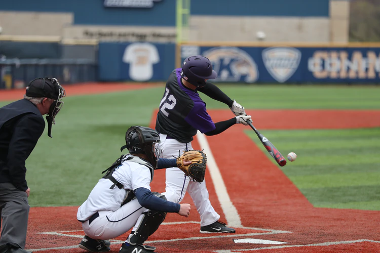 Jogador rebatendo na base durante a Liga Americana de Beisebol