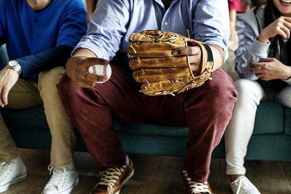 Três torcedores em casa no sofá acompanham a Liga Americana de Beisebol
