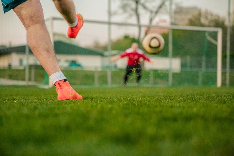 Um jogador chuta a bola em direção ao gol