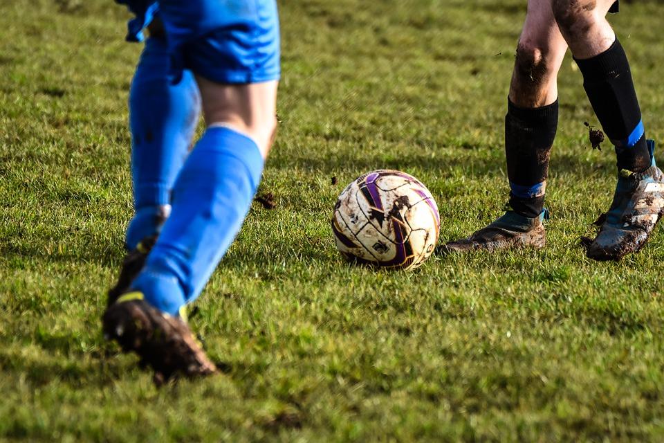 Dois jogadores disputam a bola em campo.