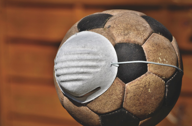 Bola de futebol com máscara de proteção em volta