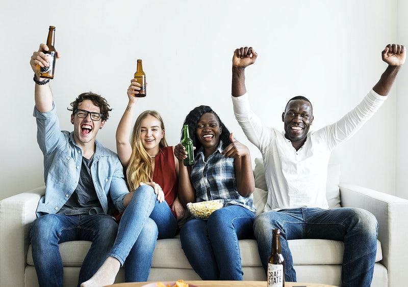 Quatro pessoas estão sentadas no sofá, erguendo os braços e garrafas de cerveja.