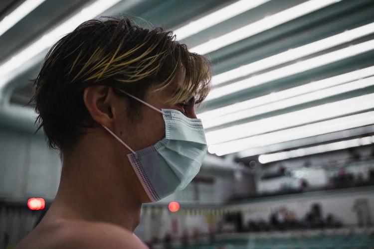 Um jovem está usando máscara olhando para a piscina