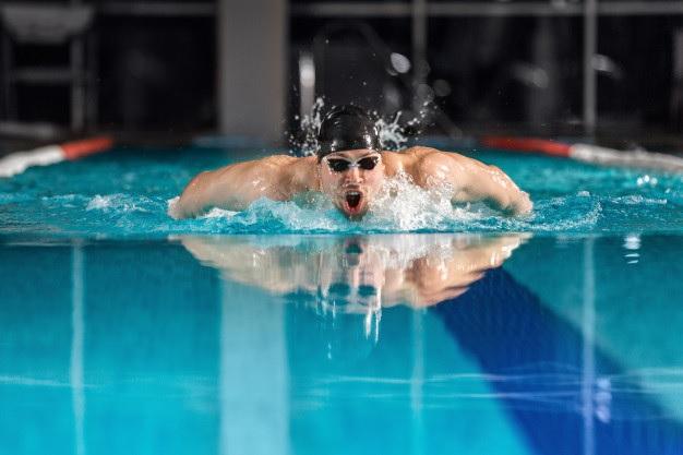 Um nadador na piscina emerge da água para respirar