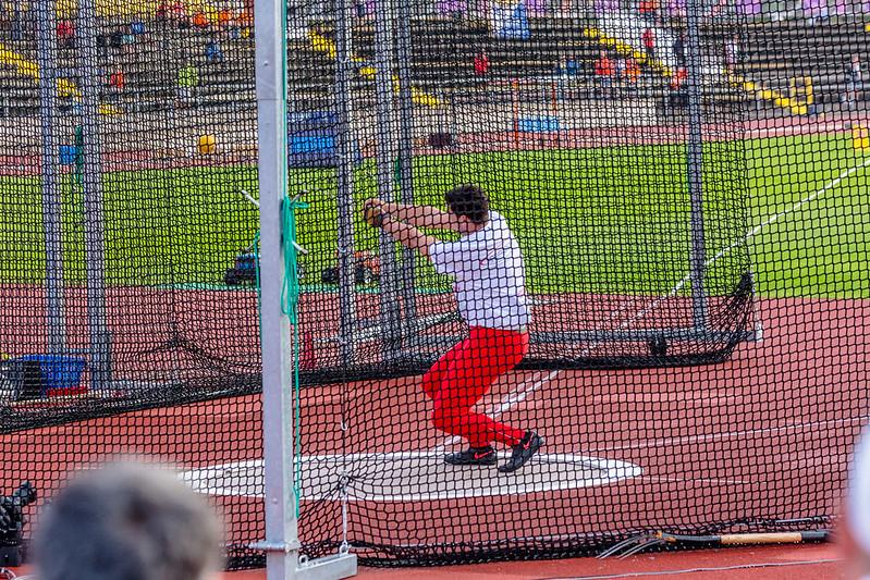 atleta de vermelho e branco no meio de giro para arremessar martelo