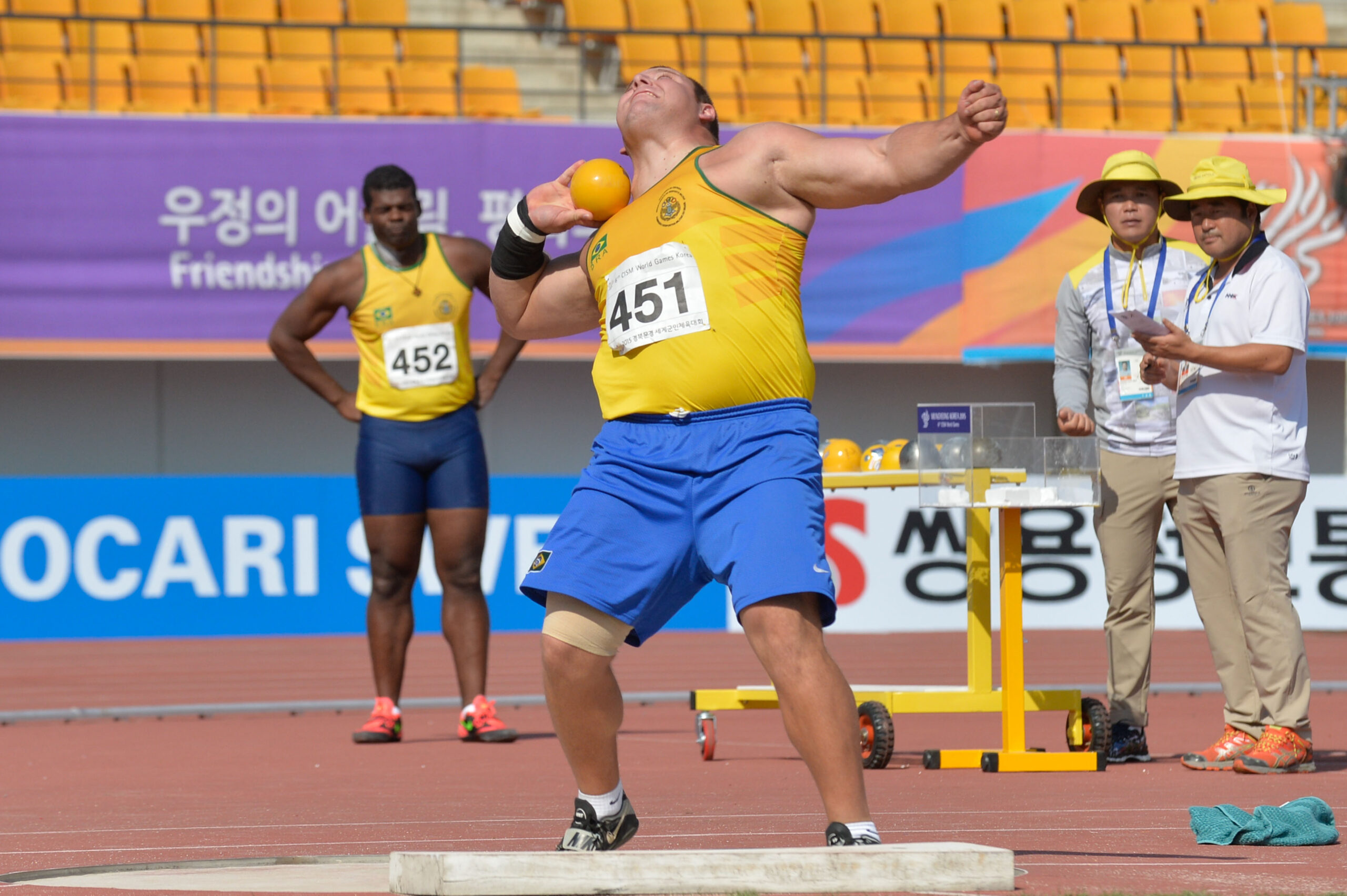 homem de uniforme azul e amarelo se preparando para arremessar peso