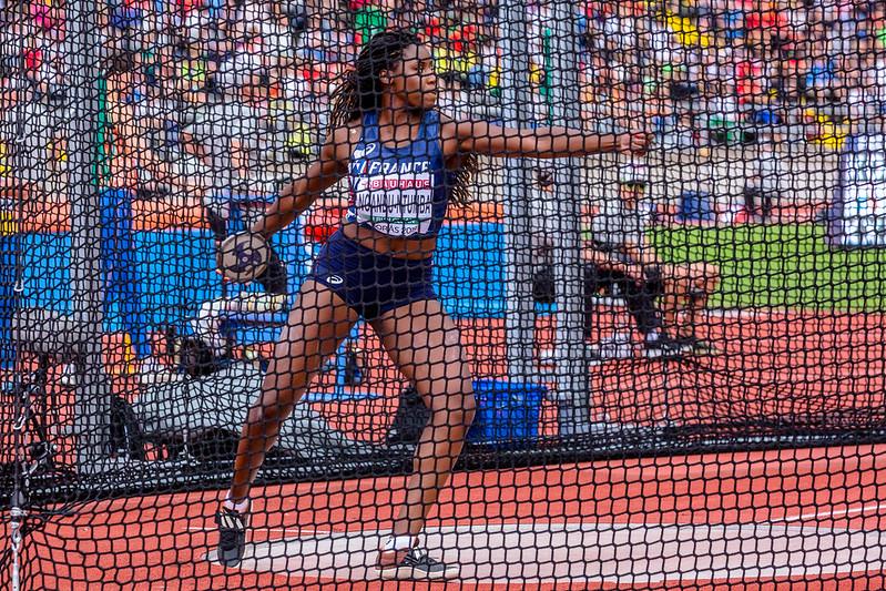 atleta dentro de rede de proteção se prepara para arremessar disco