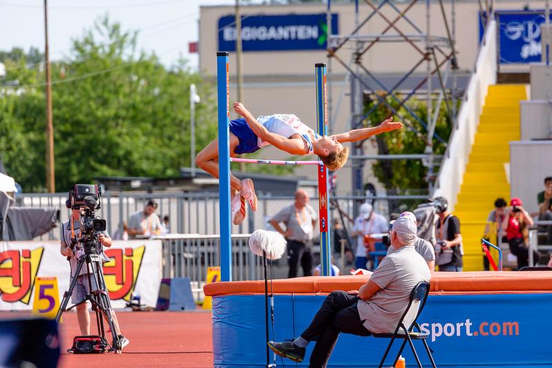 atleta saltando sob vara e caindo em colchão