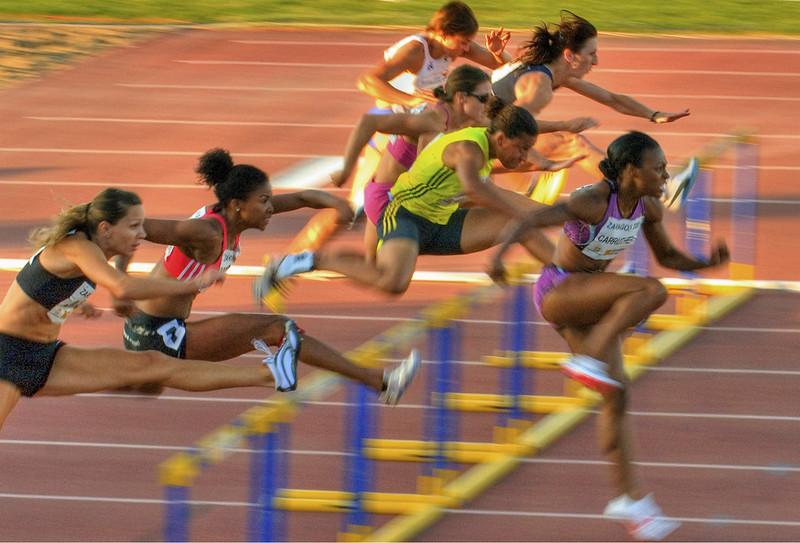 atletas correndo e saltando sobre barreiras