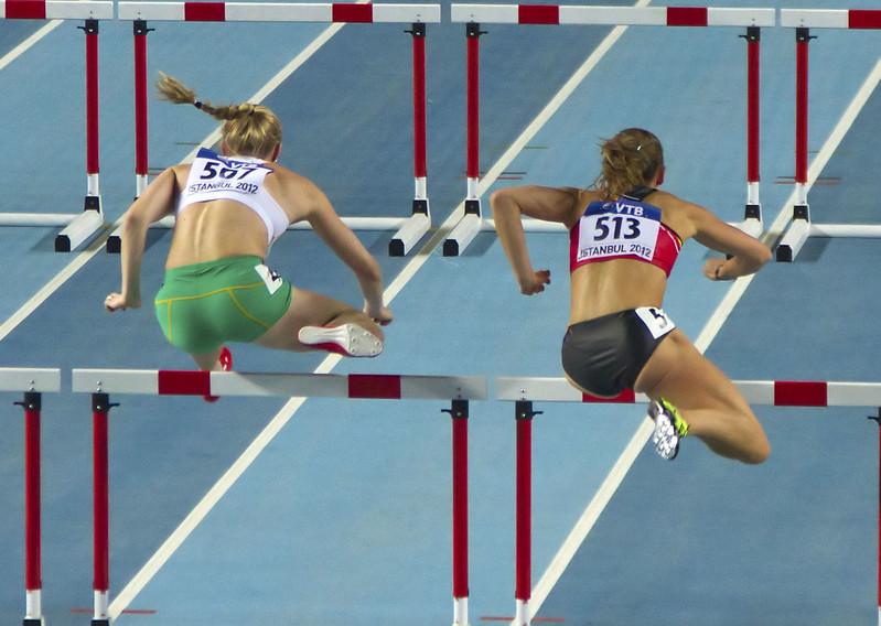 corredoras vistas de costas saltando sobre barreiras