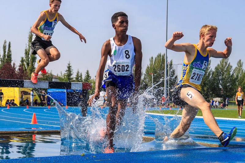 três atletas saltando sobre uma barreira e caindo em cima de um fosso de água