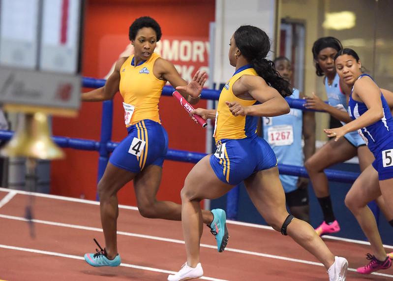 atletas femininas de azul e amarelo correndo em prova de revezamento