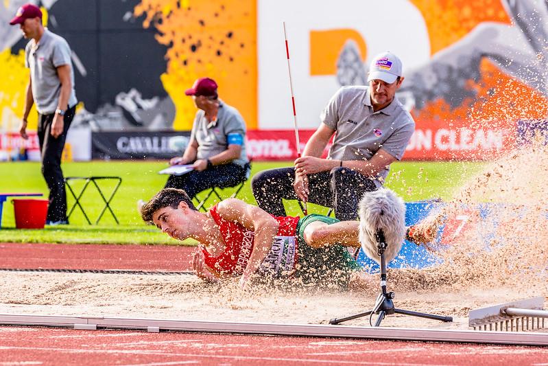 atleta caindo na areia após realizar salto triplo