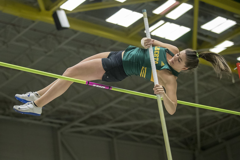 atleta de uniforme verde realizando salto com vara