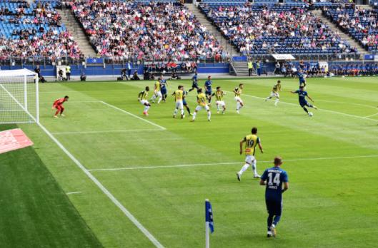 estádio de futebol com jogadores usando uniformes azul e amarelo em campo jogando