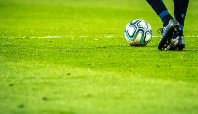 imagem dos pés de jogador em campo com uma bola com detalhes azuis do lado