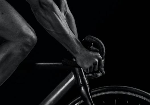 imagem ampliada em preto e branco da mão de um ciclista apoiada no guidão da bike