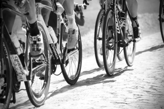 imagem ampliada em preto e branco da roda das bicicletas de ciclistas em treino