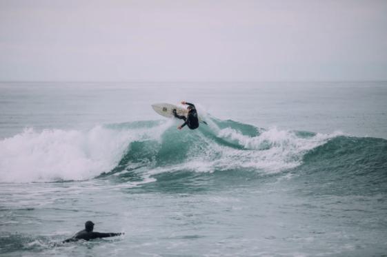 surfista fazendo manobra na onda enquanto uma pessoa nada ali perto