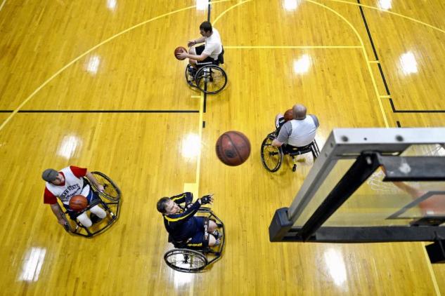 quatro jogadores paralímpicos, cada um com uma bola, treinando arremesso de basquete
