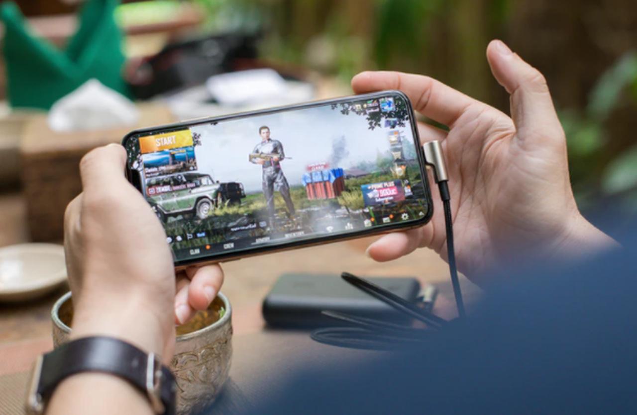 pessoa segurando celular nas duas mãos para jogar um jogo de tiro