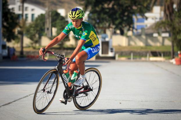 ciclista com roupa verde e azul em cima de uma bicicleta profissional em rua