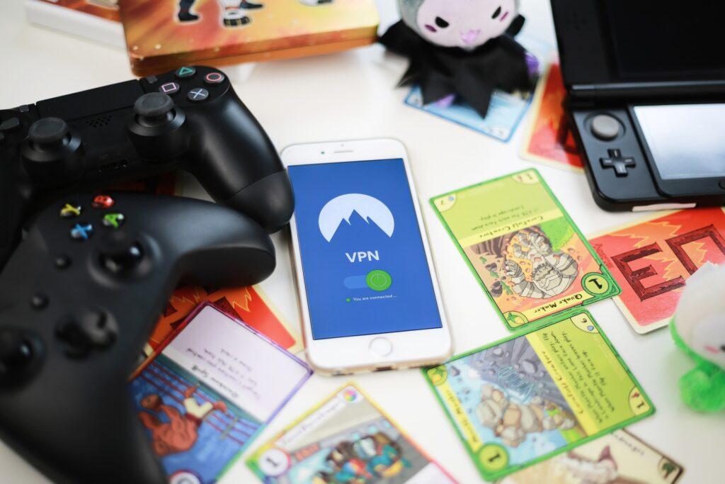 Vários controles de video games em uma mesa com um celular e e cartas da game espalhadas