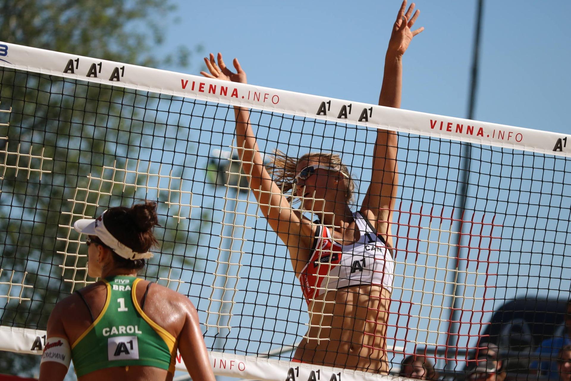jogadora de vôlei tentando rebater a bola por cima da rede