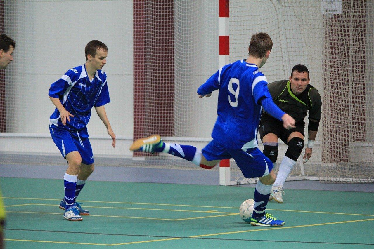 jogadores de futsal jogando esporte com um deles tentando acertar o gol