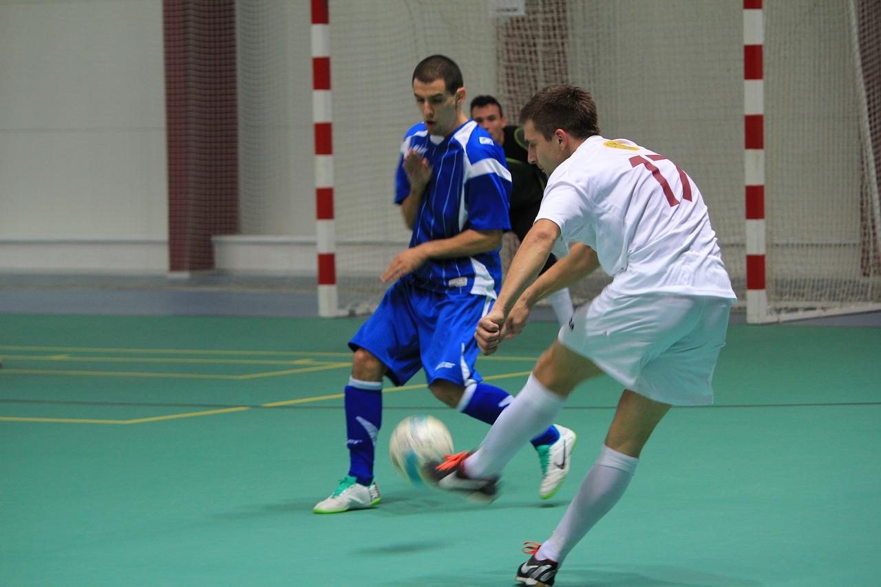 Jogadores de futsal em quadra jogando