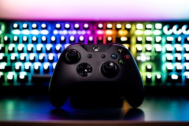 Controle de videogame diante de um painel iluminado.