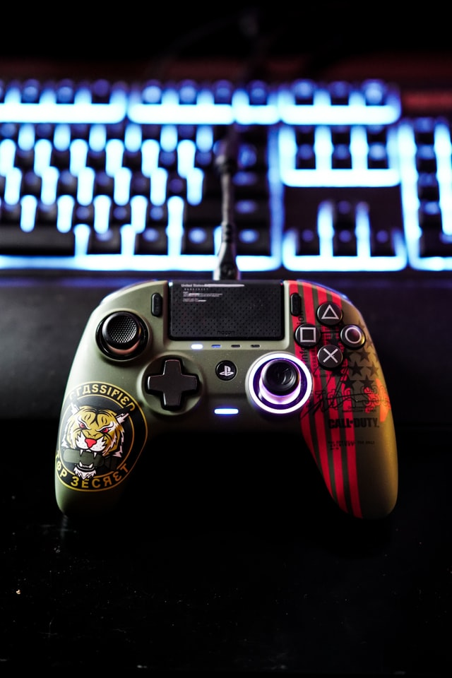 Joystick de videogame. Ao fundo, um teclado de computador iluminado.