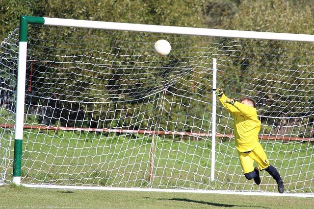 Goleiro pulando em direção à bola para fazer a defesa no gol