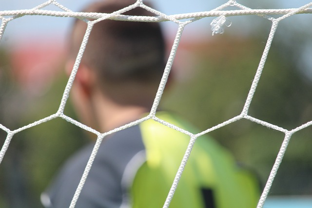 Detalhe da rede do gol com o goleiro desfocado ao fundo
